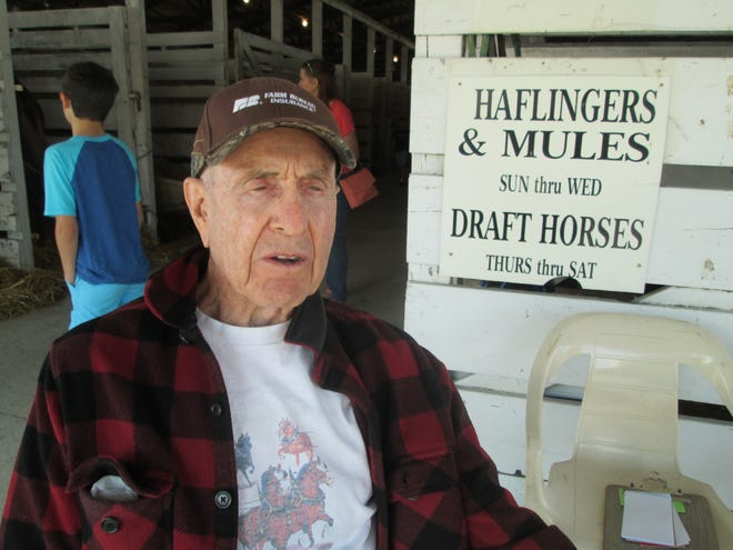 Dr. Joseph Hunt from Carleton sits near the east entrance to the draft horse barn at the Monroe County Fair Tuesday. Two mules from his Fancy Farm in Carleton are stabled there while Belgian and Clydesdale draft horses arrive today.