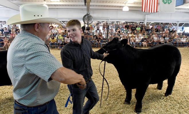 Steer 4-H judge Monte Bordner congratulates Jacob Becker, 14, of Riga when he was awarded with his heavy weight steer as the grand champion Wednesday at the Monroe County Fair.