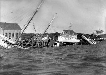 This Aug. 31, 1954, file photo shows boats driven up onto docks and buildings, and knocked into the water in the Menemsha section of Martha's Vineyard as a howling Hurricane Carol accompanied by fiercely driving rain struck New England causing millions of dollars of damage.
