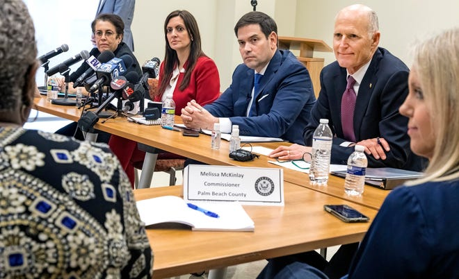 Florida Sens. Marco Rubio (left) and Rick Scott (right) listen to Palm Beach County Administrator Verdenia Baker during a press event about the coronavirus at the Palm Beach County Health Department in West Palm Beach in March 2020.