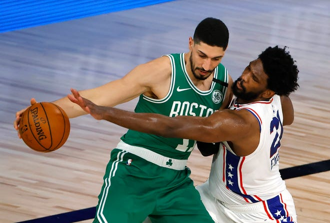 Celtics center Enes Kanter tries to keep the ball away from the Philadelphia 76ers' Joel Embiid during a game in August 2020 in Lake Buena Vista, Fla.