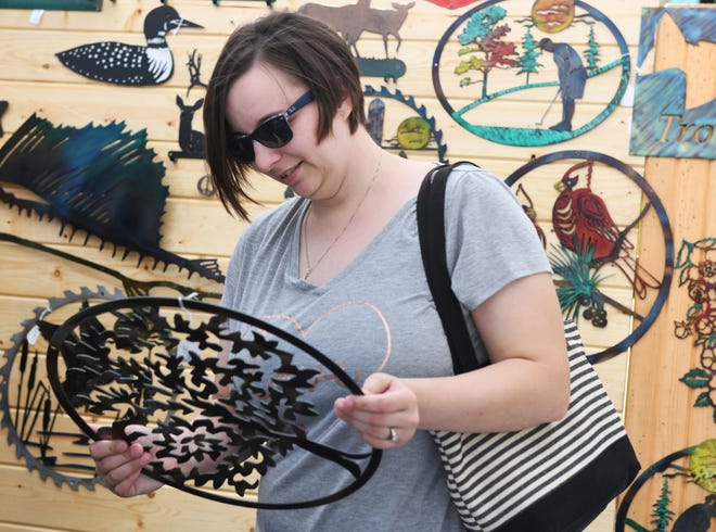 Samantha Johnson holds work from Johnny D's Custome Metal Art at the 2019 Art on Main festival in downtown Ravenna. This year's event is on Saturday.