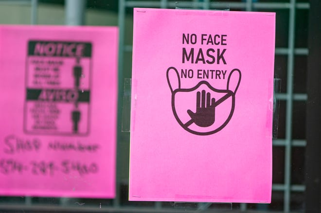 A sign requiring a face mask for entry is posted on a storefront along Western Avenue on Wednesday, Aug. 4, 2021, in South Bend.