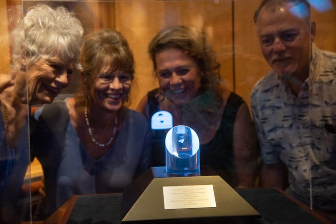 The Irwin family takes a glimpse of the NASA Ambassador of Exploration Award display at the Bishop Museum. The award was presented to James B. Irwin for his role in the Apollo 15 lunar mission.