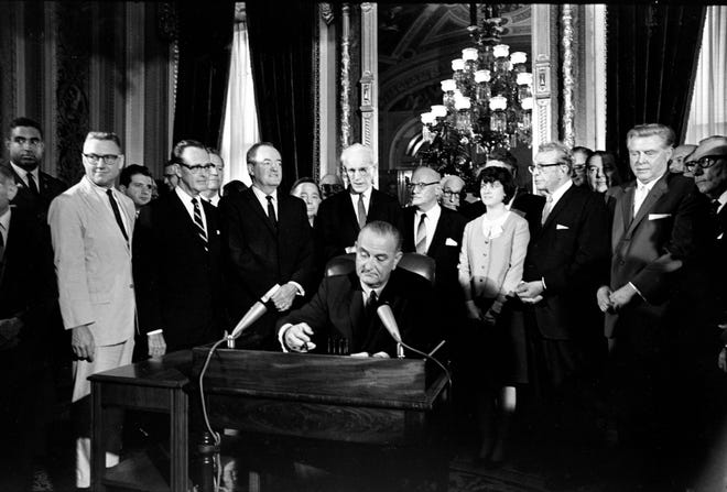 In this Aug. 6, 1965, photo, President Lyndon Baines Johnson signs the Voting Rights Act of 1965 in a ceremony in the President's Room near the Senate Chambers on Capitol Hill. Surrounding the president from left directly above his right hand, Vice President Hubert Humphrey; House Speaker John McCormack; Rep. Emanuel Celler, D-N.Y.; first daughter Luci Johnson; and Sen. Everett Dirksen, R-Ill.  Behind Humphrey is House Majority Leader Carl Albert of Oklahoma; and behind Celler is Sen. Carl Hayden, D-Ariz.
