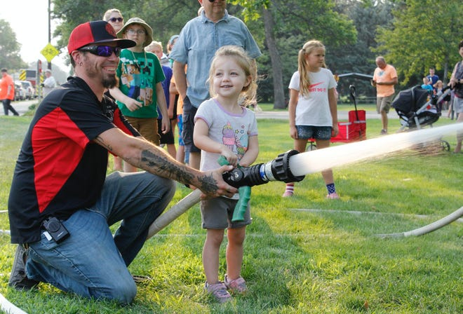 Aberdeen Rural Firefighter Tyler Brown assists Thea Conklin with a firehose during National Night Out at Melgaard Park on Aug. 3. The event was held to strengthen partnerships between police, emergency services and the community.