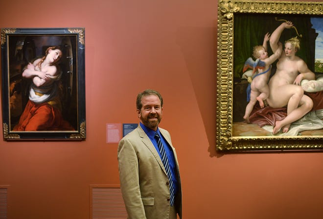 """Clark Professor John Garton, near art the students helped curate, at right, """"Venus Disarming Cupid,"""" painted about 1555, and """"Saint Catherine,"""" early 17th century."""