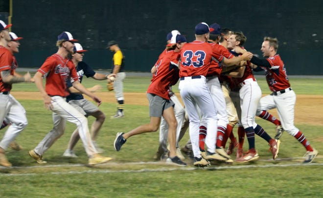 Jarrett Biesecker, second from right, is mobbed by teammates after hitting a two-run single in the bottom of the seventh inning to lift the Hagerstown Braves over the Cashtown Pirates in Game 5 of their South Penn Baseball League best-of-5 semifinal series Tuesday night at Municipal Stadium.