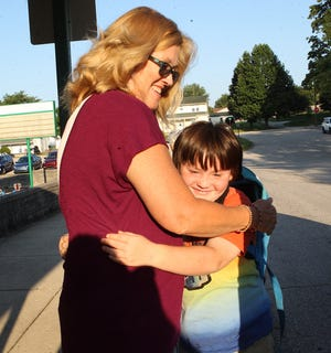 Lincoln Elementary School first-grader Austin Todd greets Lisa Cummings, Lincoln Elementary kindergarten aide with a hug during the first day of school Wednesday. Students in North Lawrence and Mitchell schools returned to school.