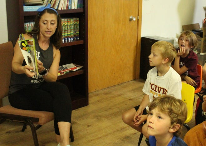 Jess Schneider reads Gizmo's Pawsome Guide to Mental Health to students at Montessori School. The book is a project available through the American Foundation for Suicide Prevention and is geared toward elementary and preschool students as a way to start conversations about mental health. Listening are, from front to back, Breken Malsom, Winston Uhlir and Josie Fischbach.