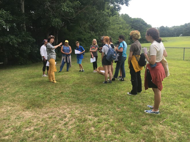 Donna Curtin, executive director of Pilgrim Hall Museum, talks to art students about the historical significance of their project on the Herring Pond Wampanoag Tribe.