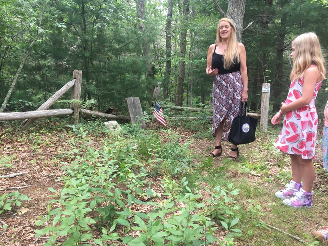 Melissa Ferretti, president and chairlady of the Herring Pond Wampanoag Tribe, talks about the history of Dina Path, a Native burying ground in Cedarville. Ferretti's granddaughter, Ava Hannigan, looks on.
