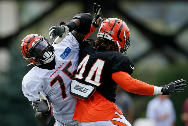 Cincinnati Bengals linebacker Darius Hodge (44) pushes around offensive tackle Isaiah Prince (75) during a training camp practice at the Paul Brown Stadium training field in downtown Cincinnati on Wednesday, Aug. 4, 2021.