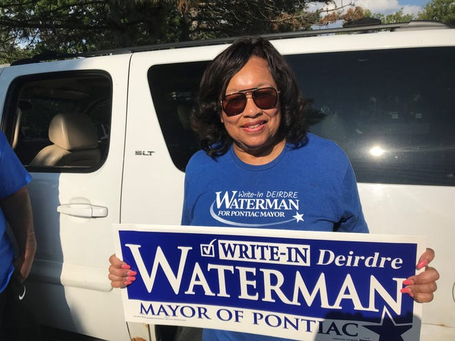 Pontiac Mayor Deirdre Waterman shows off one of her campaign signs, which instructs voters to write in her name, as Waterman stands outside polls at the Baldwin Community Center on primary election day: Aug. 3, 2021. (Photo: Bill Laitner)