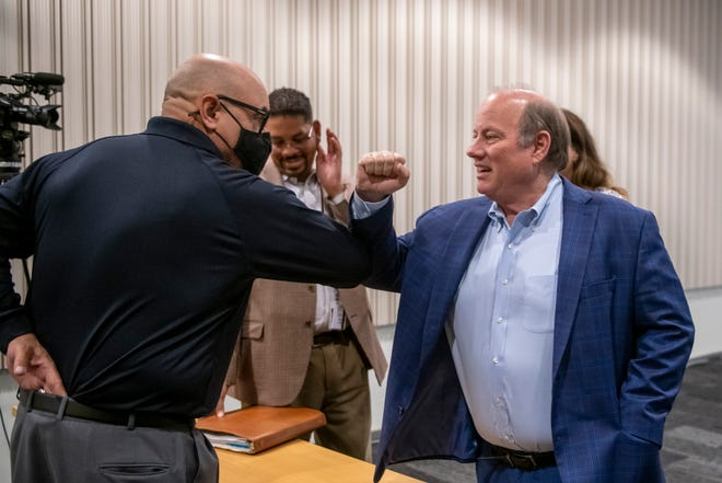 Detroit Mayor Mike Duggan, right, says hello to Scott Burgess, a federal coordinating officer with FEMA, before the start of a press conference at Detroit Public Safety Headquarters, in Detroit, August 4, 2021, to explain the step-by-step process of applying for flood relief for damage from the storm of June 25th-26th.