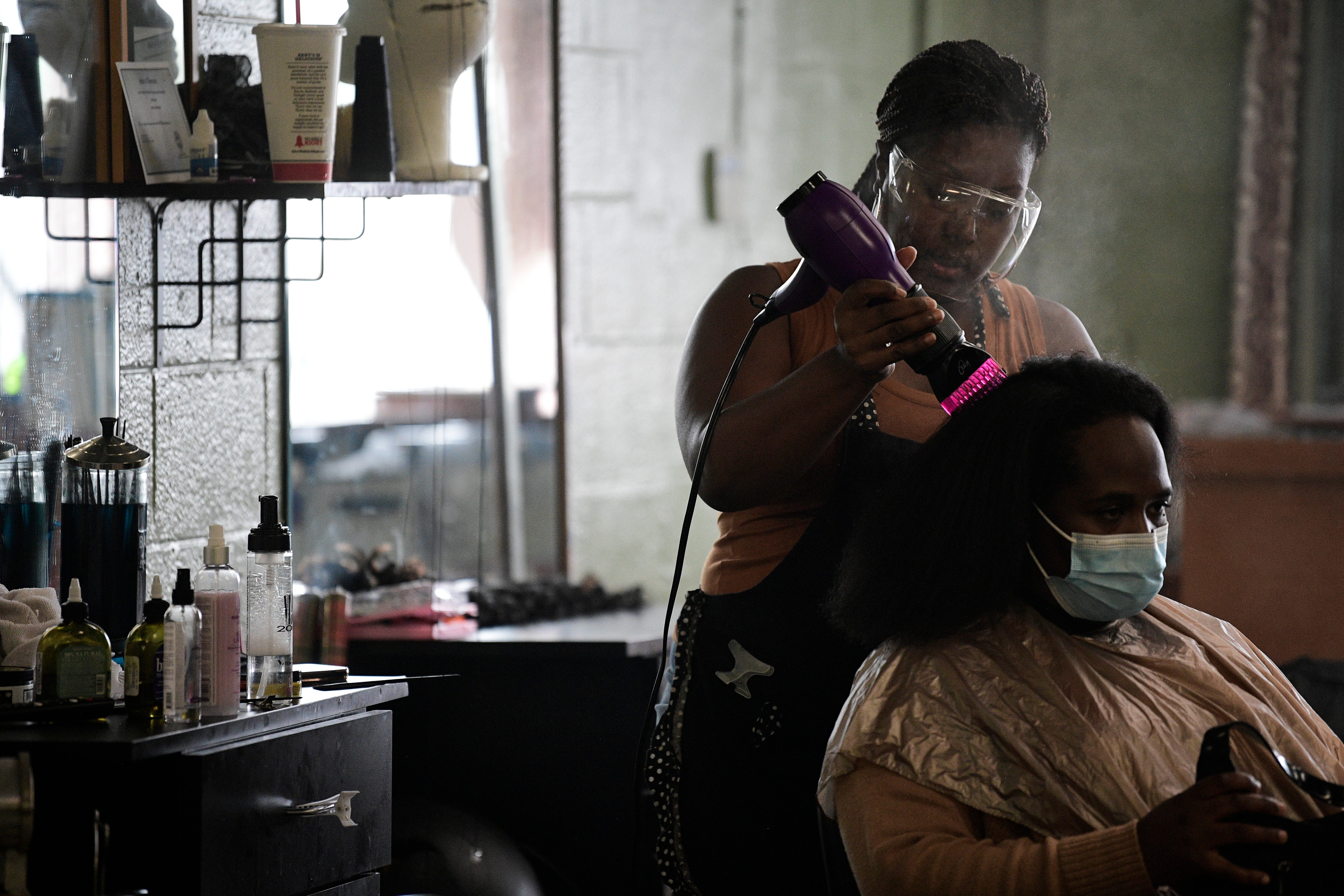Chanta Barfield cuts the hair of a client named Denissa Smith