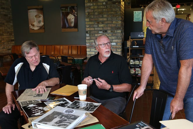 Band members from 50 years ago, James Finn, left, who plays keyboard, drummer Gregory Samuels, center, who inspired the Gregory James Group band, and Rich Kayser, right, who plays bass, look at photos and news clippings from their band's career on July 21 on the Marquette University campus. The devastation of COVID-19 inspired Samuels, a retired dentist in Madison, to reunite with the band 50 years after he left the group.