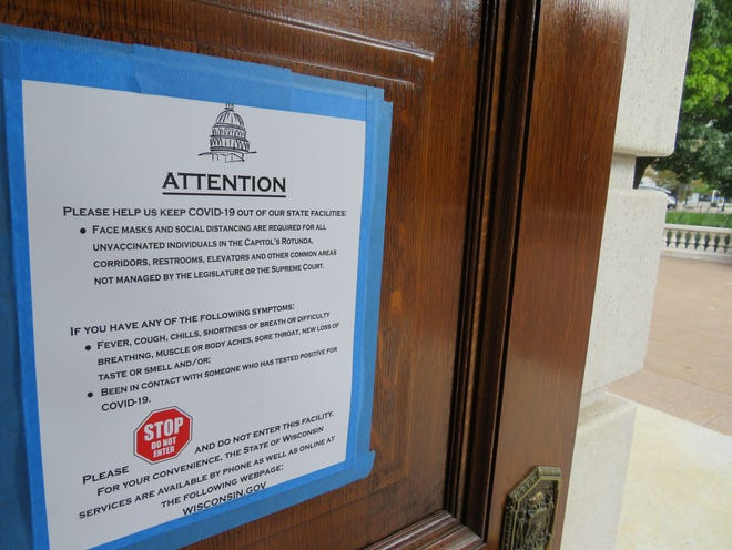 A sign on the door of a state Capitol entrance states that face masks and social distancing are required for unvaccinated people in certain areas of the building.
