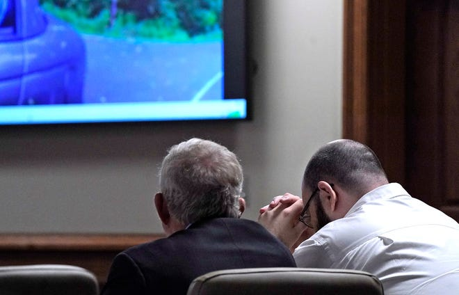 Steven Wiggins who is charged with first-degree premeditated murder and first-degree felony murder in the shooting death of Sgt. Daniel Baker buries his head in his hands as body camera footage is shown where he shot Baker.