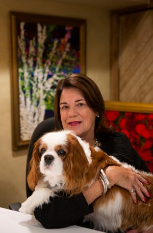 """Newark based artist Sallie Cochran sits in her studio with her Cavalier King Charles Spaniel Charlie in front of her painting """"Birches at Night"""" at her home in Newark, Ohio on August 3, 2021. Cochran will be auctioning the painting off to help the Newark Granville Symphony Orchestra."""