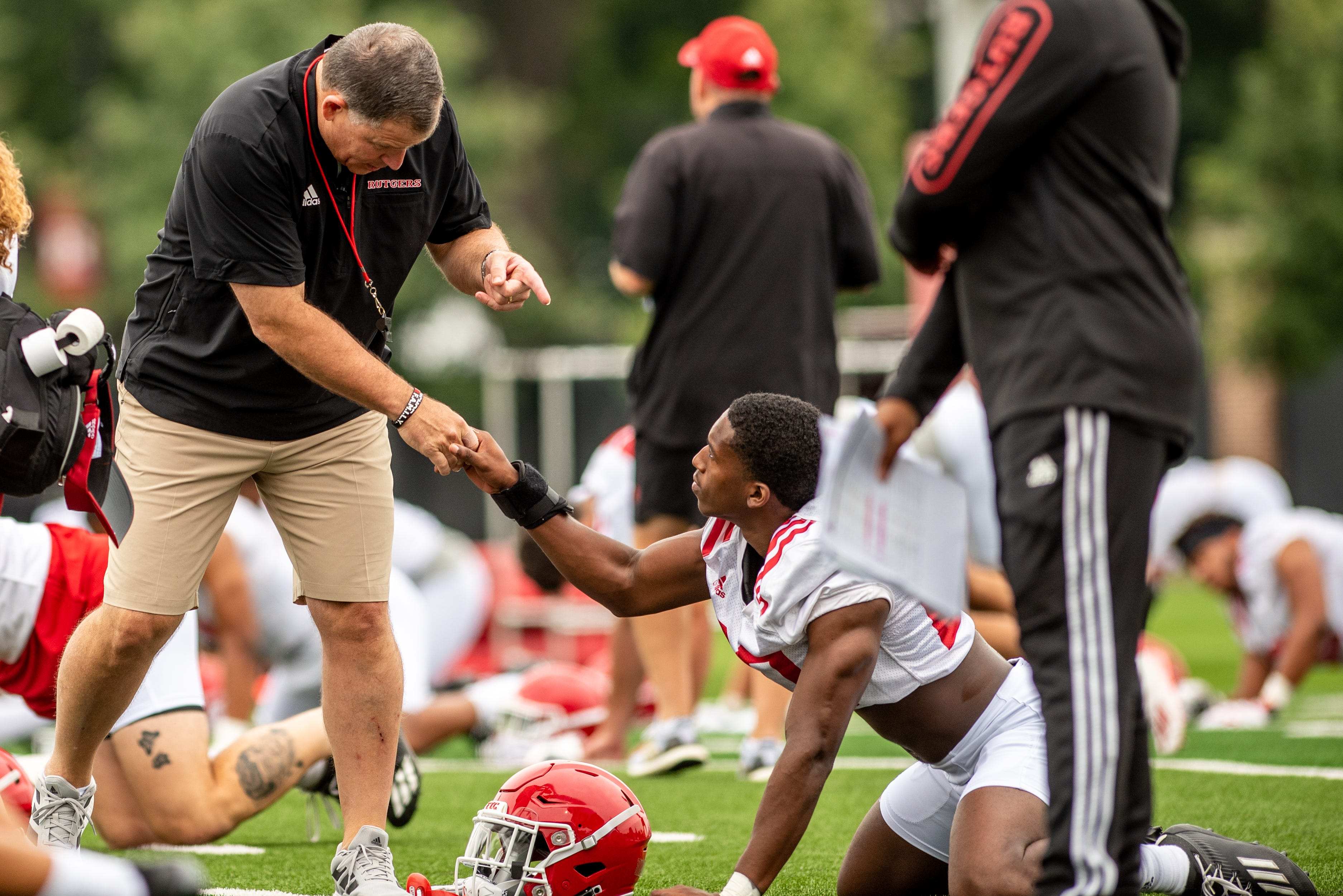 Rutgers football's first practice of training camp is held In Piscataway on Wednesday August 4, 2021. Head coach Greg Schiano shakes a player's hand during practice.