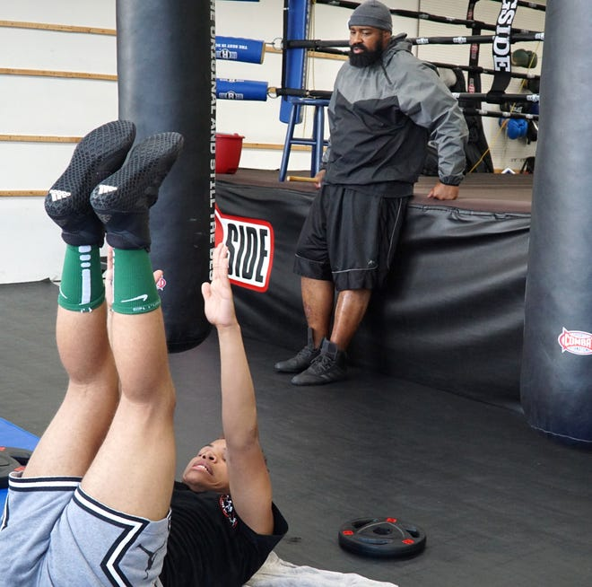 Trainer Darnell Baldwin, right, works with some students at the MMA House of Champions in Livonia on Aug. 4, 2021.