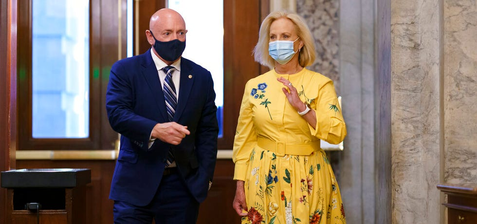 Sen. Mark Kelly, D-Ariz., is joined by Cindy McCain, the widow of the late Sen. John McCain of Arizona, as Kelly arrives to deliver his maiden speech to the Senate at the Capitol in Washington on Aug. 4, 2021.