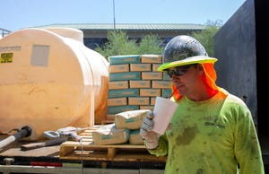 Yellow Jacket Drilling Services worker Josh Alster drinks from a cup while taking a break from work near downtown Phoenix on Aug. 4, 2021.