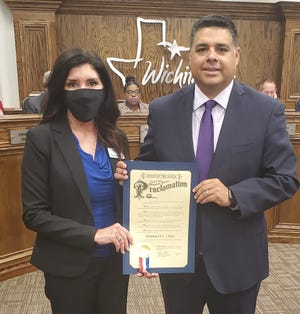 Atmos Energy Manager of Public Affairs Pam Hughes Pak and Wichita Falls Mayor Stephen Santellana are seen with a proclamation at Tuesday's City Council Meeting, declaring August 11 as National 811 Day, to bring awareness to the importance of calling 811 before digging.
