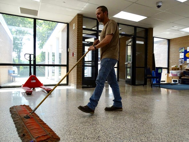 Wielding a dust mop, custodian Sean Finnerty cleans the floors of Duncan Falls Elementary on Aug. 4, 2021. It's less than three weeks from the first day of class, and the custodial staff is back at work sanitizing the school ahead of students' return.