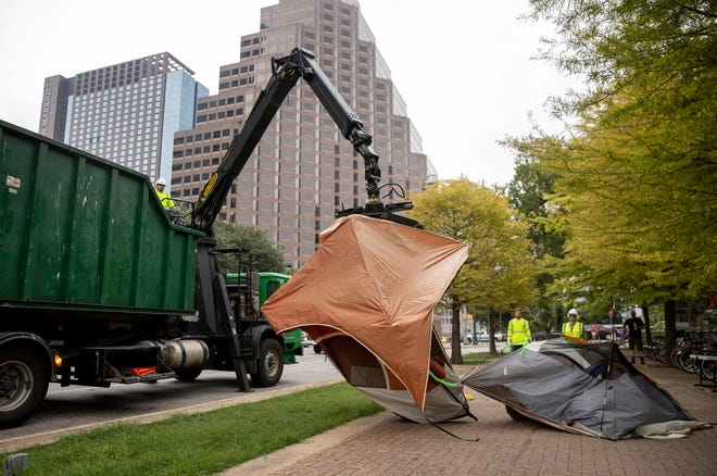 Austin Resource Recovery workers remove tents Aug. 5 during a partial clearing of a homeless camp on West Cesar Chavez Street.