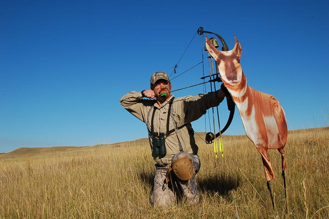 Tom Opre draws his bow behind a decoy on the prairie of eastern Montana.