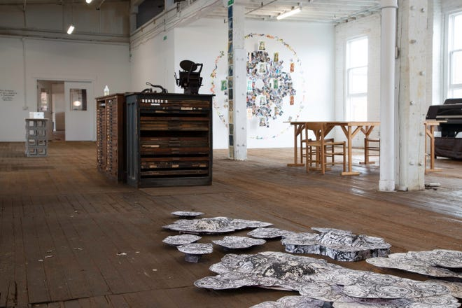 """""""Spatial Exposure,"""" an exhibition of Print Fellows from Columbus Printed Arts Center, located on the second floor of The Fort on the far South Side. Catie Beach's """"Neoplasm"""" covers the floor, while Alissa Ohashi's circular """"Source"""" installation is seen on the far wall."""