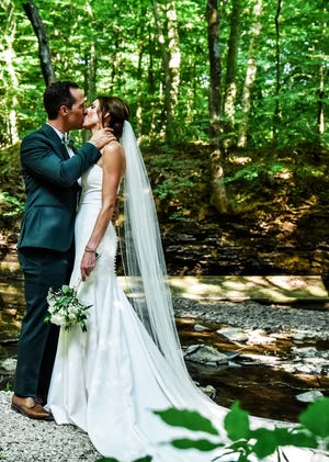 Steven and Chloe Starkey kiss near the brook for which their new wedding venue is named. The Marion couple was the first to be married at the Brook, a Marengo event space they helped open to give couples more options in where they marry.