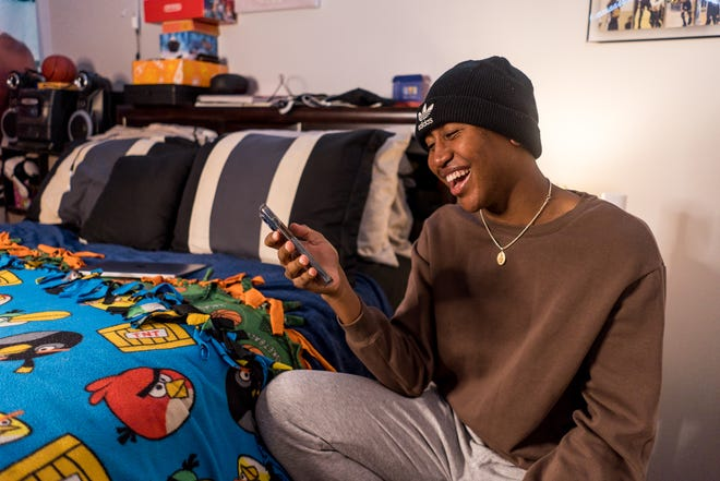 Ron Cox Jr., of Bourg smiles after realizing Team USA gymnast Jordan Chiles, an Olympic silver medalist, left a comment on one of his TikTok videos. He does most of his video work in his bedroom.