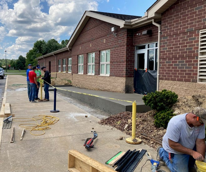 Cambridge City Schools employees work to complete a handicapped-accessible ramp at Cambridge Intermediate School prior to the start of the 2021-22 school year. The ramp was requested by a teacher in the building.