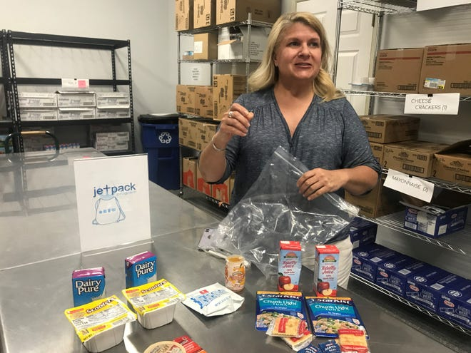Anne Marie Stern, director of JetPacks, at The Well Outreach in Spring Hill packs nonperishable food items in a plastic bag so that food insecure students in Maury County and Williamson County schools will have extra sustenance over the weekend.