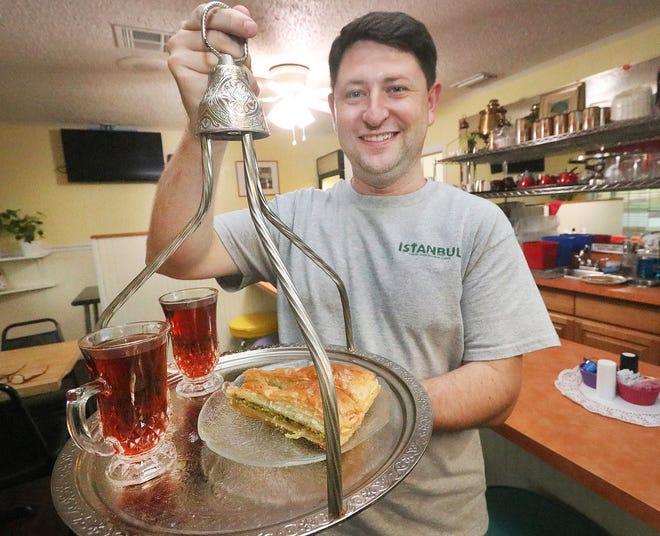 İstanbul Türk Akdeniz restoranının sahibi Wesley Huber, 4 Ağustos 2021 Çarşamba günü Ormond Beach'te bir tepsi çay ve baklava tutuyor.