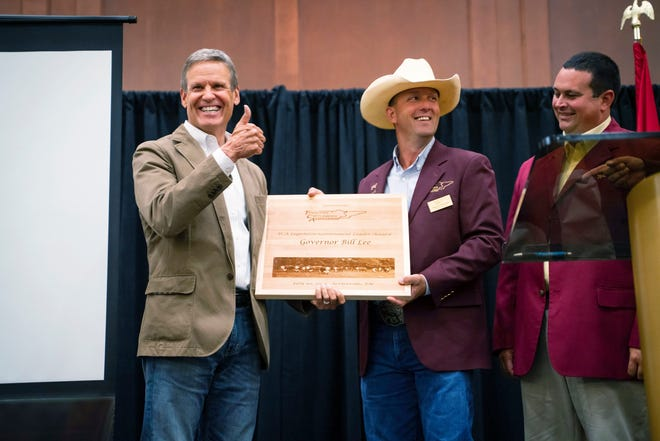 This photo provided by the State of Tennessee shows Tennessee Gov. Bill Lee receiving an award from Dustin Pearson, Tennessee Cattlemen's Association President-Elect at the Tennessee Cattlemen's Association annual convention on July 30, 2021 in Sevierville, Tenn.