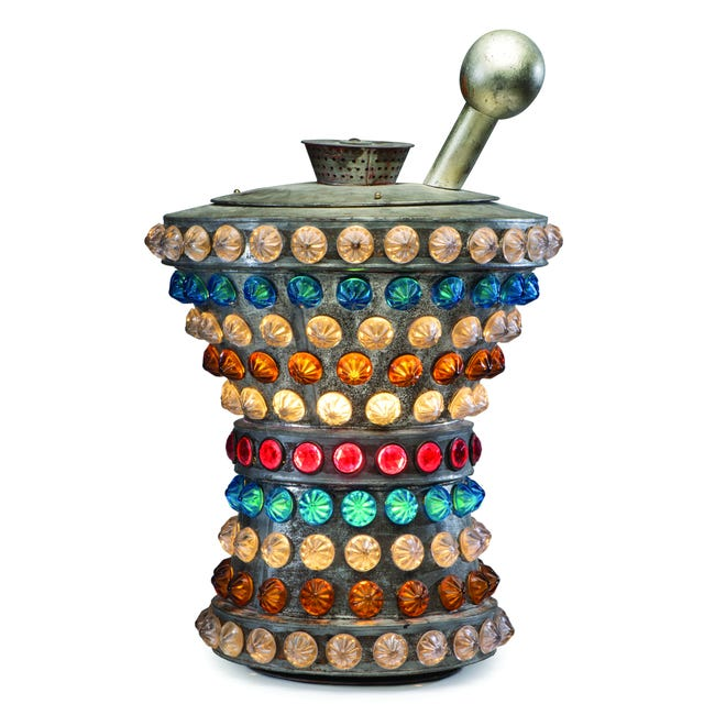 This 1920s apothecary sign shaped like a mortar and pestle is 20 inches high, made of tin with cut and colored glass mounted to the outside. It sold at Cowan's for $8,125.