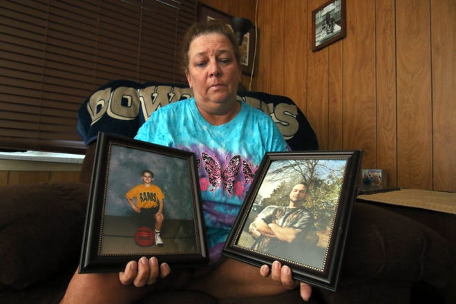 Melony Lewis holds two photographs of her son, Brad Murray, who was struck by a car and killed along U.S. 74 in April.