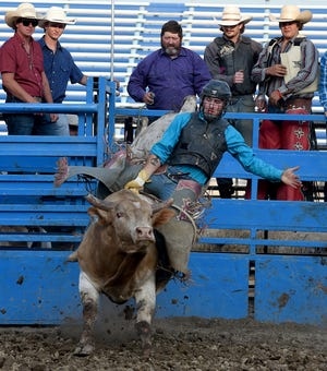 Professional bull rider Matt Allgood of Saline rides a bull named Diesel in the Lost Nations Rodeo, held Wednesday at the Monroe County Fair.