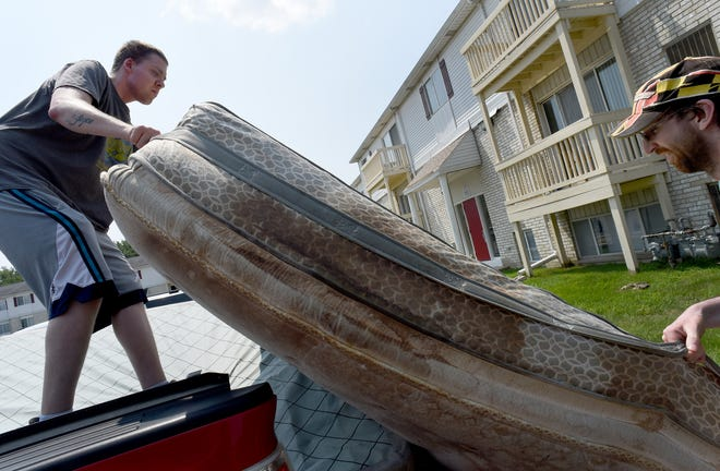 Chris Engle (left) with the help of a friend loads up a damaged mattress that he will have to put into storage as he and other tenants are being evicted from the sub-level units at Sterling Pointe Apartments in Monroe.