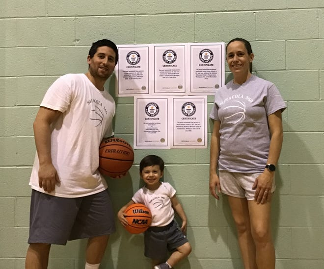"""Anthony Miracola of Temperance (left) poses with his wife Jennifer, son Anthony IV and his five Guinness Book of World Records certificates. He won a sixth award after the photo was taken. He hopes go get up to """"15 to 20"""" in the next few years."""