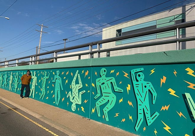 """Joe Slack is pictured with his art, """"Birdwatching OKC Lightning Thunder Dance Party,"""" which can be found along Classen Boulevard, between Seventh and Ninth Streets."""