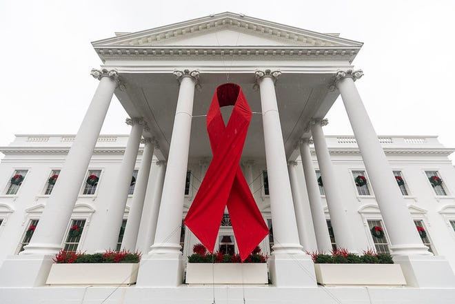 A red ribbon hangs from the North Portico of the White House for World AIDS Day Saturday, Dec. 1, 2018.  Official White House Photo by Keegan Barber