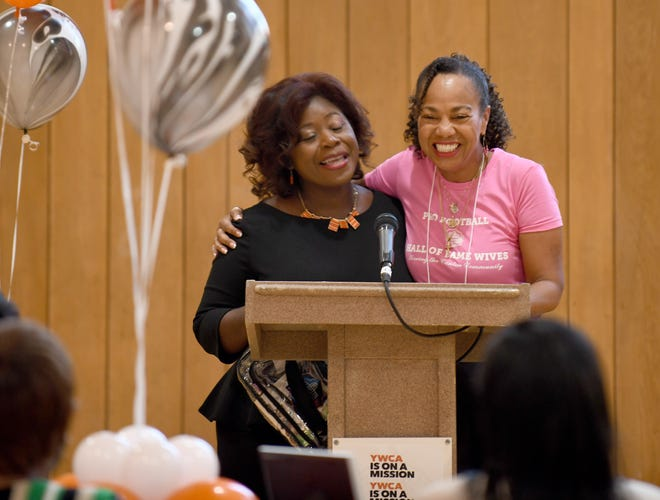 Shana Smith, executive director of Canton YWCA, greets guests with DeBorah Little, wife of Hall of Famer Floyd Little, prior to a panel discussion and children's storytime at the Canton YWCA.