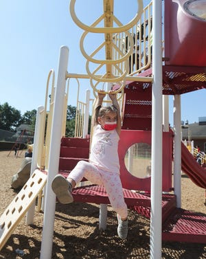 Teddy Shimek, a first grader at Canton City Schools' AIM Academy at Belden, tries her hand at the monkey bars during recess at the school.