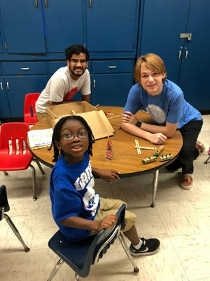 Manas Adepu of Nease High School (right) and Roberto Lachner of Ponte Vedra High School (left) volunteer with the Community-in-School program in Jacksonville which helps underserved and at-risk students in the area.