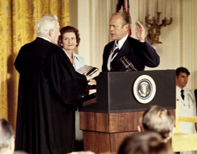 Gerald Ford, right, takes the oath of the office of the presidency, from Chief Justice Warren Burger as Ford's wife, Betty, looks on Aug. 9, 1974, in Washington, D.C. The oath was administered in room where only hours before, Richard Nixon bid farewell to his staff.